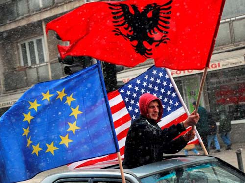 An Ethnic Kosovo Albanian waves European union, US and Albanian flags from a car in Pristina on February 16, 2008. Kosovo will declare independence on February 17, amid growing excitement among its ethnic Albanians, anger from its Serbs, and the launch of an EU mission to smoothen the birth of the world's newest state. AFP PHOTO / DIMITAR DILKOFF