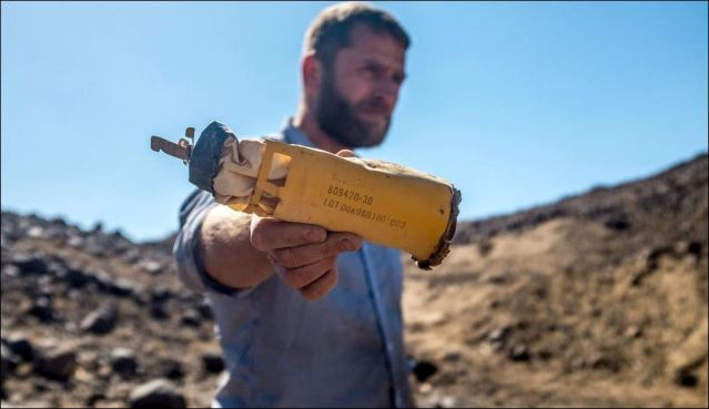VICE correspondent Ben Anderson holds a spent cluster bomb near the Razamat farm in Sadah, Yemen. (Photo by Peter Salisbury/VICE News)