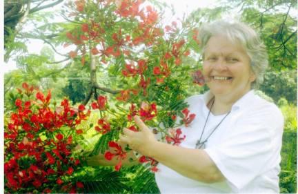 Бразил, биолог поред процветале биљке Flamboia
