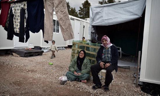 Мигранти седе поред кућа-контејнера, избеглички камп у северном делу Атине, децембра 2016. (Photograph: Louisa Gouliamaki/AFP/Getty Images)