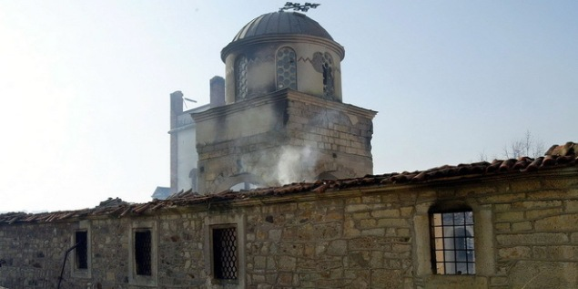 epa00156262 Smoke rises from a smouldering Orthodox church, after it was burned by ethnic Albanians during a demonstrationin central Pristina, Kosovo, Friday 19 March 2004. The United Nations Security Council demanded an immediate halt to 'large scale inter-ethnic violence' in Kosovo that has left 31 people dead and 500 wounded. EPA/VALDRIN XHEMAJ