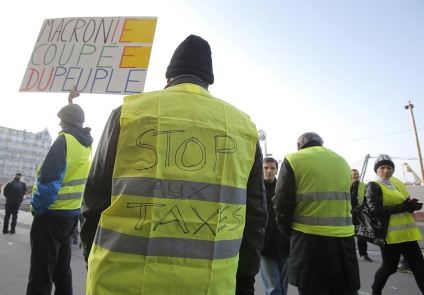 Demonstrators gather to protest fuel taxes in Paris, France, Tuesday, Nov. 17, 2018. France is bracing for a nationwide traffic mess as drivers plan to block roads to protest rising fuel taxes, in a new challenge to embattled President Emmanuel Macron. Placard reads, Macron your cut off from people. (AP Photo/Michel Euler)