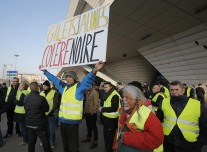 Demonstrators gather to protest fuel taxes in Paris, France, Tuesday, Nov. 17, 2018. France is bracing for a nationwide traffic mess as drivers plan to block roads to protest rising fuel taxes, in a new challenge to embattled President Emmanuel Macron. Placard reads, yellow jacket black anger. (AP Photo/Michel Euler)